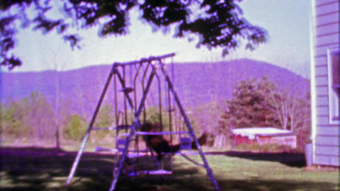 1968: Boy swing set in country rural mountainous setting Live Action