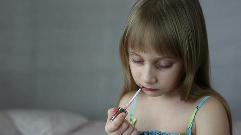 Little girl paints lips with lipstick Footage
