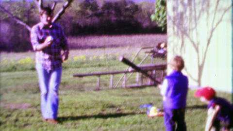 1968: Dad pitching baseball to sons practicing backyard fun Footage