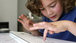 Boy typing on a white keyboard Live Action