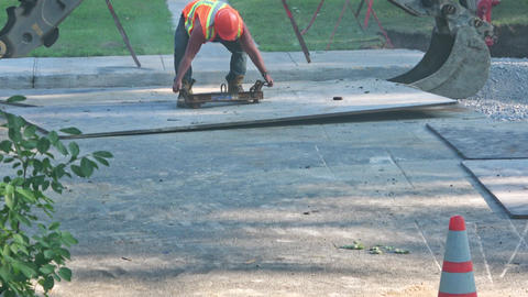 City worker attaches steel clamp to steel plate Footage