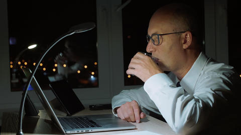 Adult businessman drinking water from glass and working by laptop in night Footage
