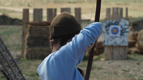 Girl archer preparing for a shot from the bow Strong wind interferes with the Footage