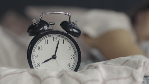 Young woman is woken by her alarm clock Footage