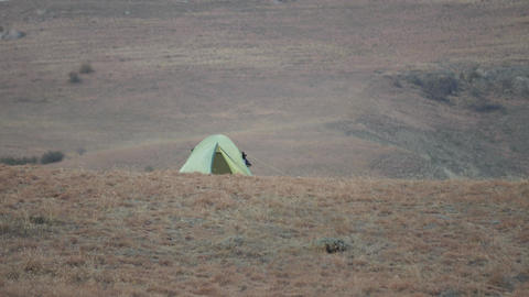 a green tent stands on top of a red hill The mountain wind blows on top Live Action