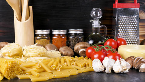 Variety of raw pasta on table next to other ingredients for dinner Archivo
