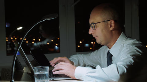Executive businessman using laptop computer while working overtime in dark Footage