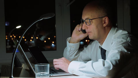 Concentrated businessman working on laptop and talking by… Stock Video Footage