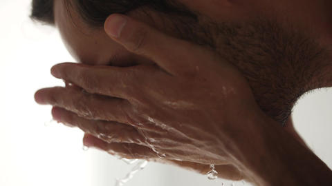 A man is washing his face with water Slow motion video Footage