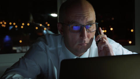 Serious businessman using mobile phone for business conversation in dark office Footage