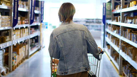 Woman shopping at the supermarket, follow shot from back of young woman with Footage