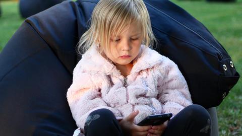 Little girl watching cartoons in phone Footage