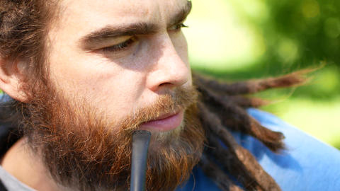 Portrait of hipster man with dreadlocks smoking cigarette. Side view Live Action