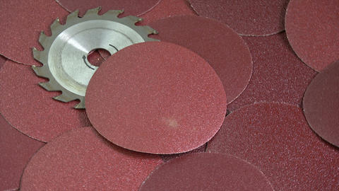 Rotating sanding discs and circular saw tool industrial equipment background Live Action