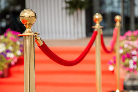 Golden rope barrier with red event carpet フォト