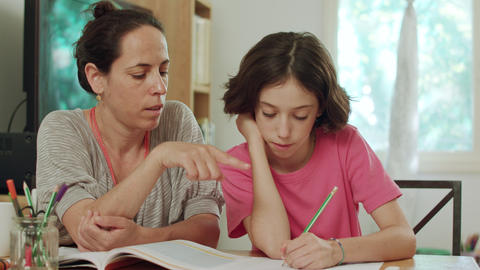 Mother helping her daughter to prepare homework at home Live Action
