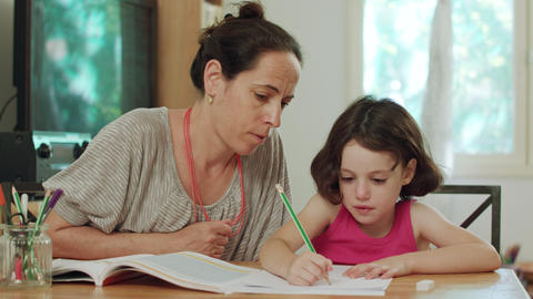 Mother helping her little daughter to prepare homework at home Footage
