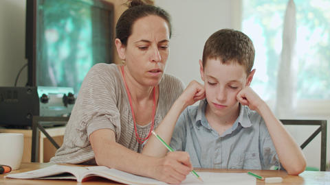 Mother helping her son to do his homework at home GIF
