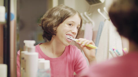 young girl brushing her teeth in front of the mirror GIF