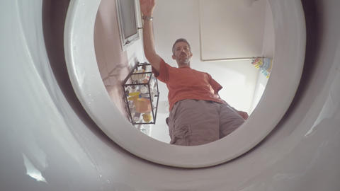 A view from inside the toilet with water flushing down Live Action