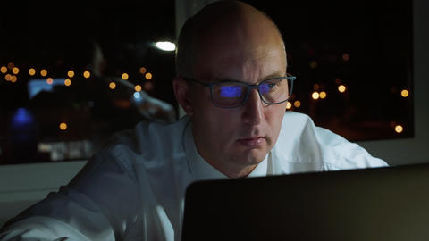 Executive businessman in eyeglasses looking at laptop workig late in evening GIF