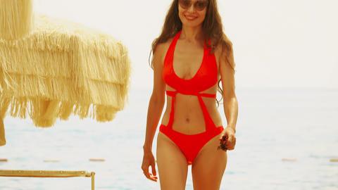 Beautiful young woman in orange bikini walks on the beach Archivo