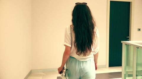 Beautiful woman walks in a modern hotel hallway and atrium GIF