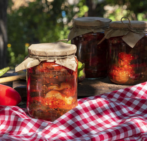 Canned eggplant slices in spicy vegetable sauce in glass jars Fotografía