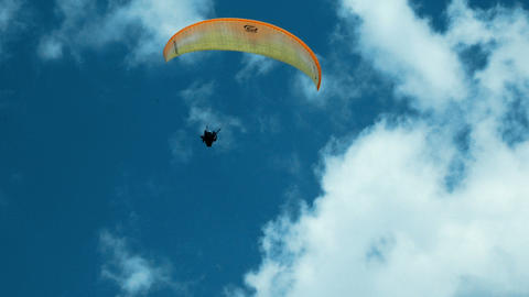 paraglider flies over a mountain top in South Tyrol Archivo