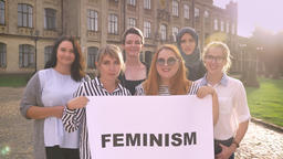 Various group of young caucasian feminists standing with sign and smiling Footage