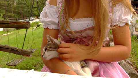 Teen dressed in typical Tyrolean dress caresses a small kitten Footage