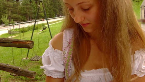 Teen dressed in typical Tyrolean dress caresses a small kitten Photo