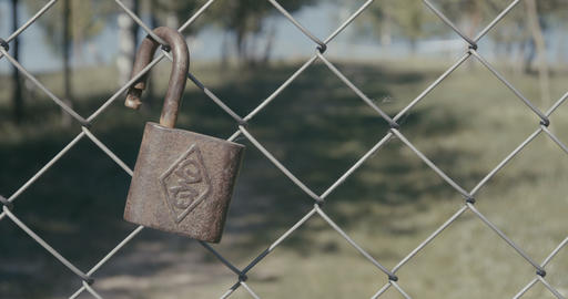 4K - metal lock hanging on a fence in the background of a beautiful landscape GIF