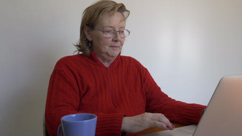 Middle aged woman using her laptop in a room Footage