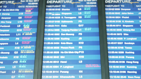 Backpacker checking flight information on digital schedule display in iairport Footage
