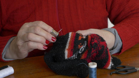 Adult woman sewing a sock by hand Footage