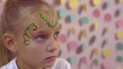 Cute girl teenager receiving multicolor face aquagrim with glitter and diamonds GIF