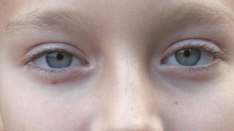 Teenager with gray eyes looking in camera closeup. Children face with gray eyes Live Action