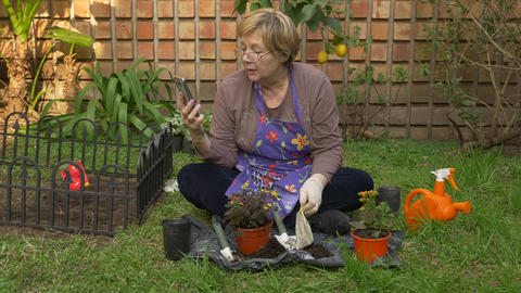 Adult woman answering a video call while working in her garden Footage