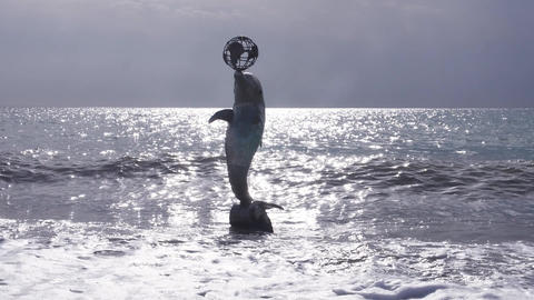 A dolphin monument with a globe on its nose against a background of sunlight Live Action