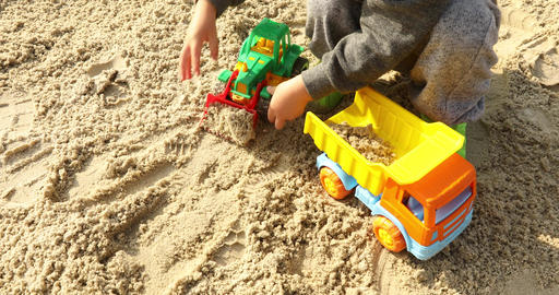 Kid playing raod works with toy excavatorin in sand Footage