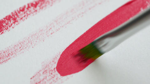 Drawing with a paintbrush on white paper with bright pink acrylic paint close up Footage