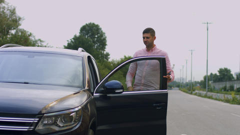 Handsome casual man getting into luxury car GIF