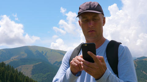 Adult man using mobile phone in mountain landscape, low angle view Live Action