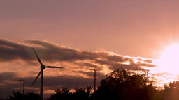 Sun setting with a wind turbine propeller in silhouette. Collecting sustainable 영상물