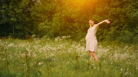 Pregnant woman dancing in the field at sunset Stock Video Footage