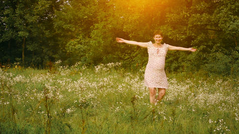 Pregnant woman dancing in the field at sunset Footage