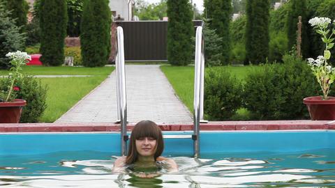Pretty girl in bikini swimming in the pool Stock Video Footage