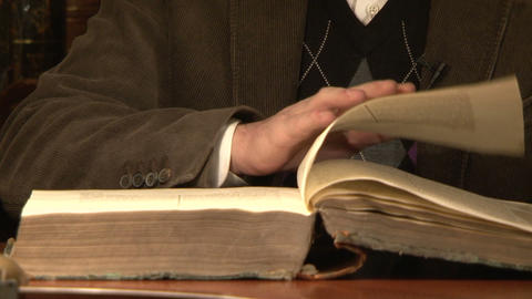 The man flips through an old book Footage