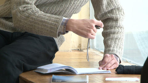 A student with a book at the table Stock Video Footage